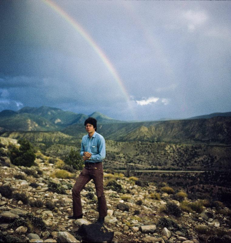 Man standing alone in foreground with rainbow and mountains in the background