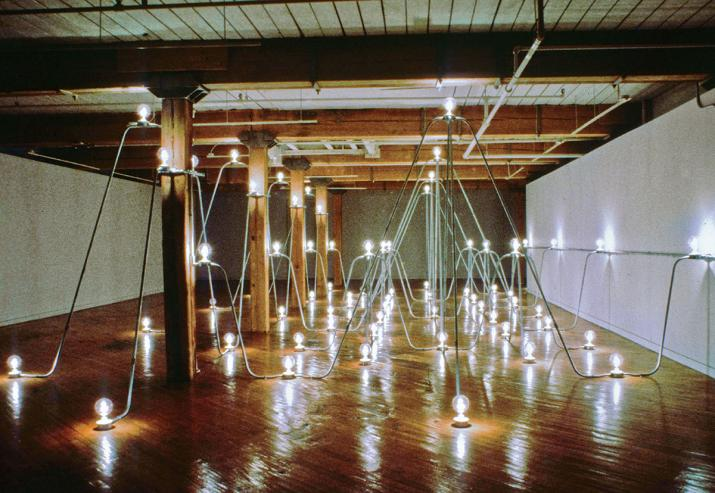 A series of interconnected steel conduit and lightbulbs in a room.