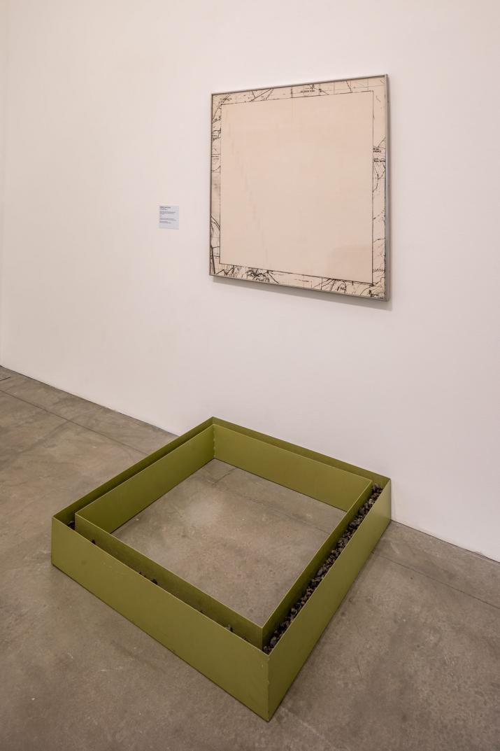 wall and floor with a square map on the wall and a square metal box of the same shape and size on the floor