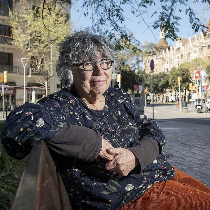 Woman with gray hair and glasses sitting on a bench looking at the camera.
