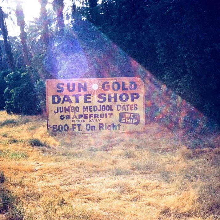 "A sign in a sunny clearing that says ""Sun Gold Date Shop"""
