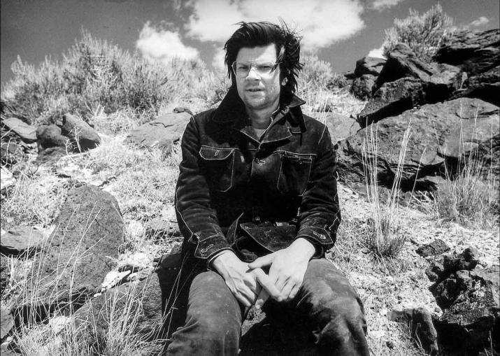 A balck and white photo of Robert Smithson at the site of the Spiral jetty in 1970.