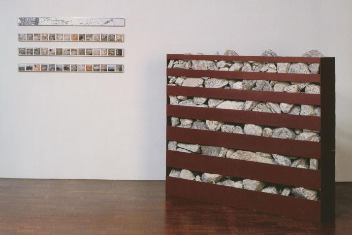 A metal box filled with rocks and horizontal slots cut in the box on the floor and horizontal images on the wall.