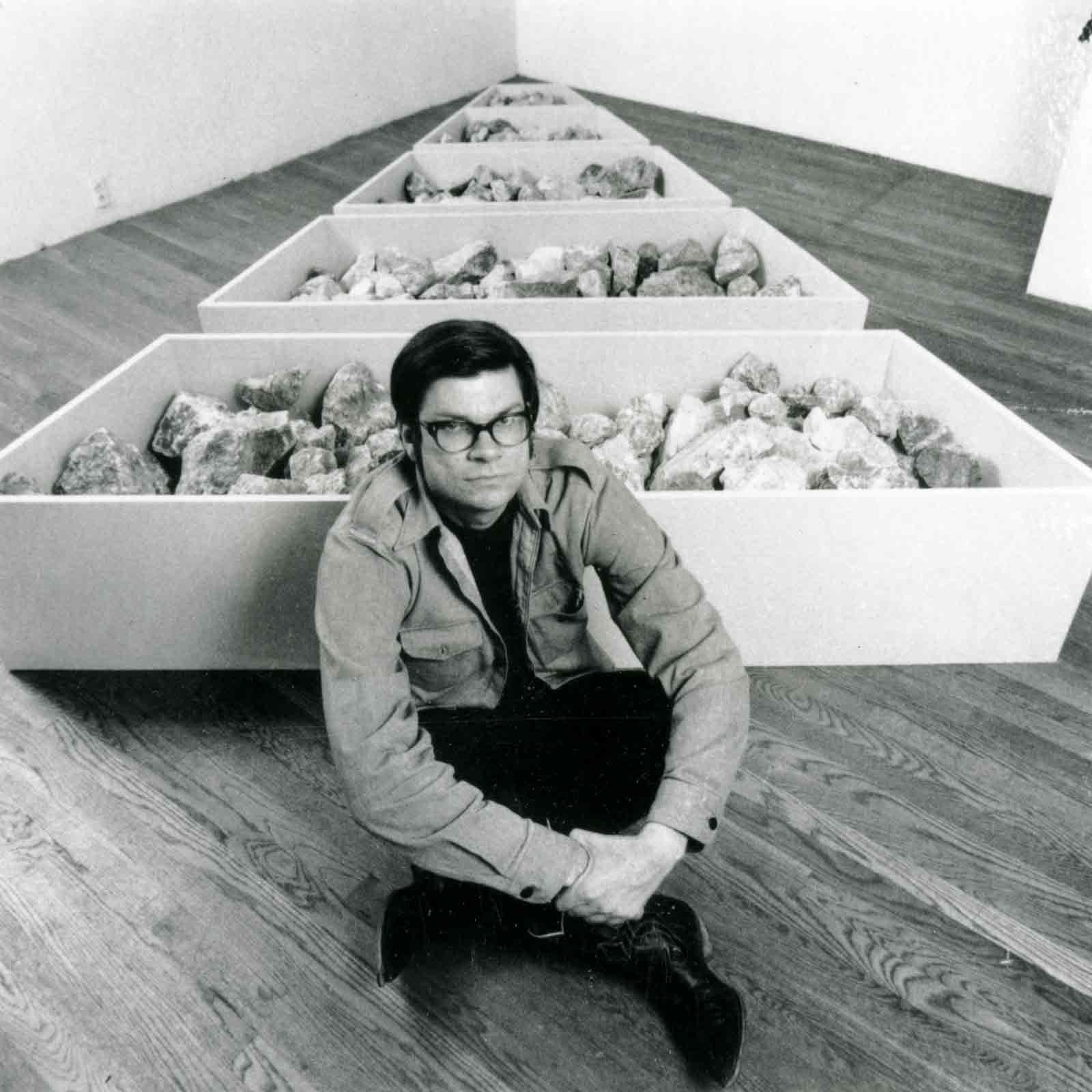 Robert Smithson, in a gallery environment, next to his work, Franklin Nonsite
