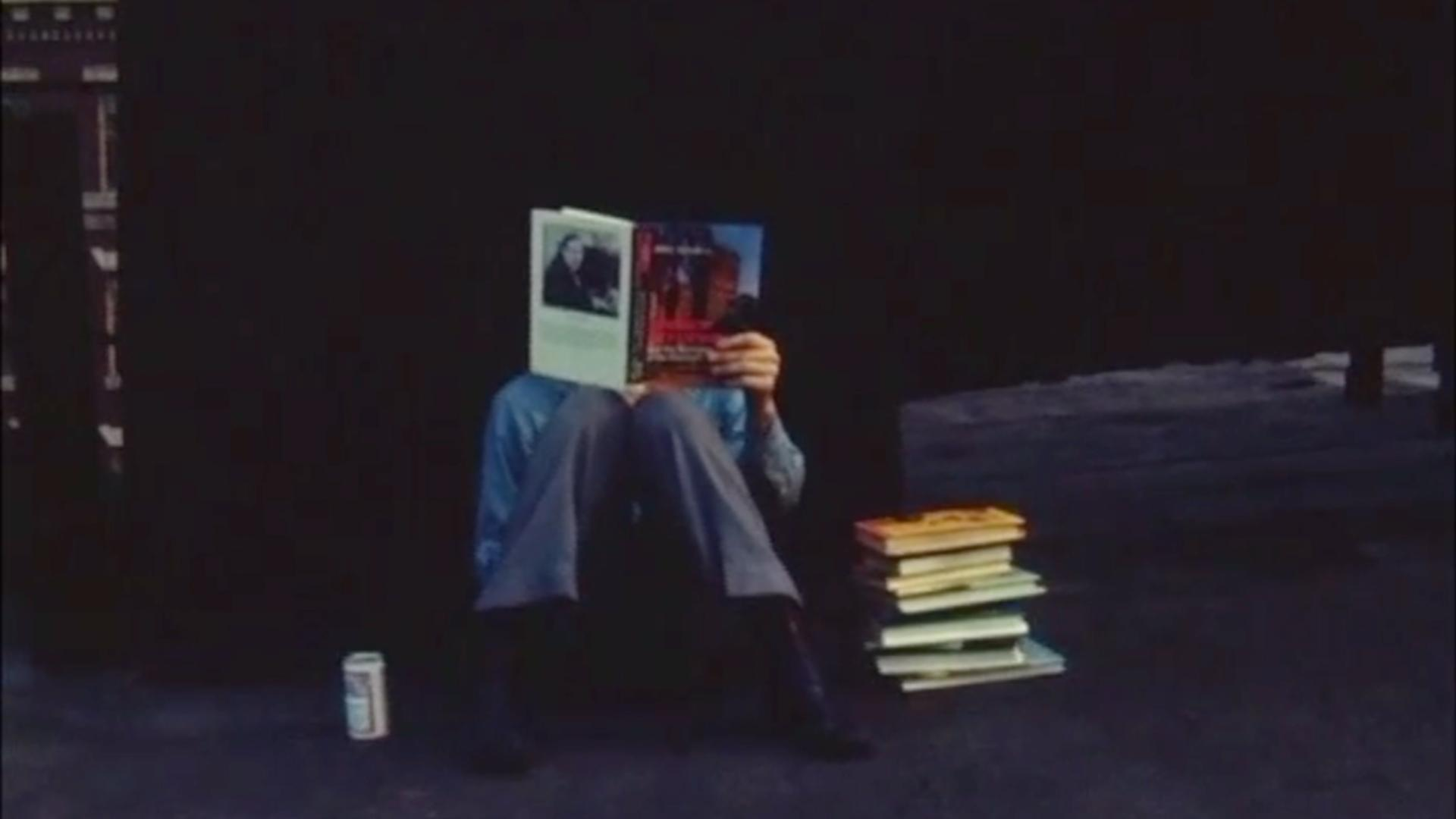man sitting on the ground reading a book with a pile of books next to him